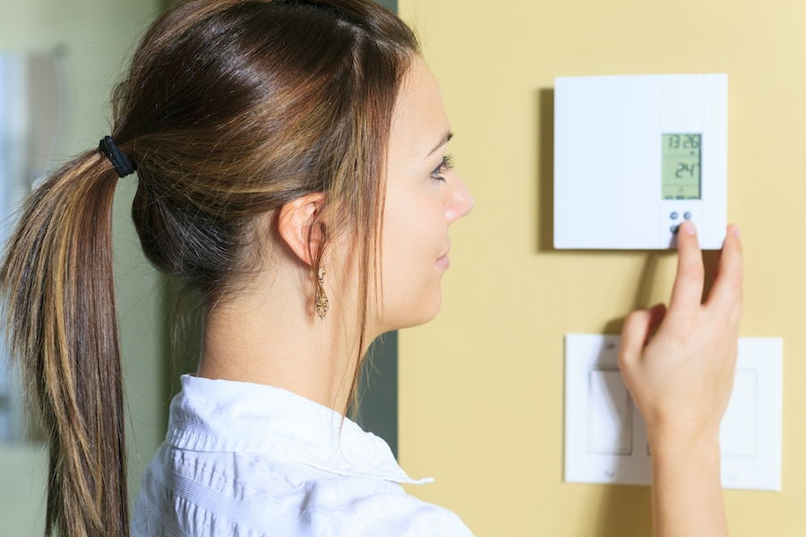 Woman adjusting the thermostat in her western Washington home.