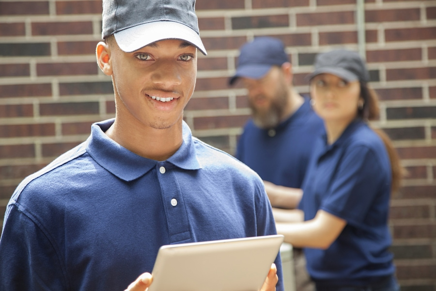 Multi-ethnic group of two men and one woman repairing a home's air conditioner unit outdoors. African descent man in foreground uses a digital tablet to access the repairs. They all wear blue uniforms.