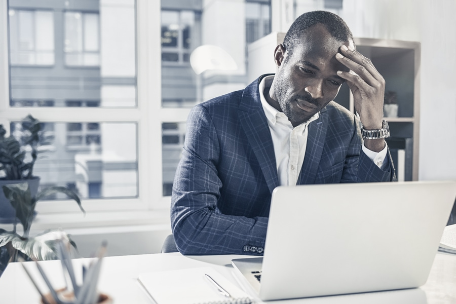 Feeling headache. Tired young serious african american businessman is sitting at desk and touching his head while expressing weariness. He is looking at screen of modern laptop with concentration.