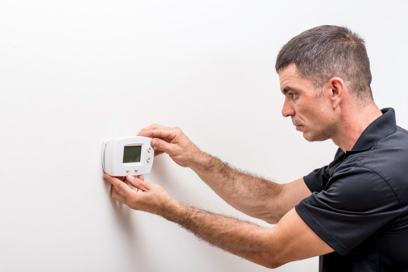Man Fixing Thermostat