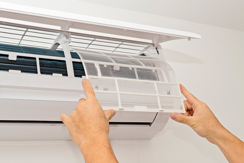 A pair of hands opening the panel of a ductless system | What Maintenance Is Needed For a Ductless System? | Seattle, WA
