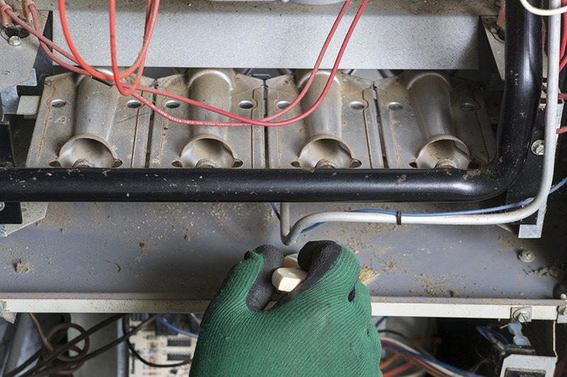 A gloved hand repairing the inside of an appliance | 5 Reasons to Schedule a Fall Furnace Clean and Check | Kent, WA